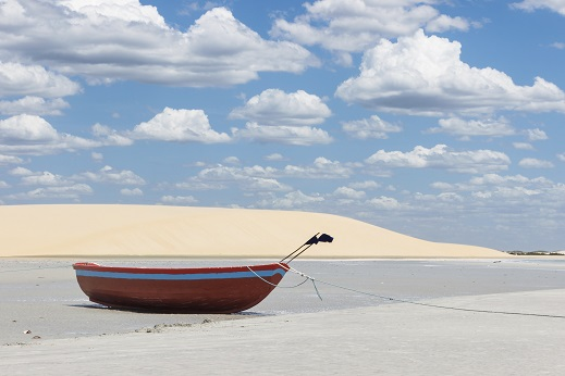 Little boat with dune and beautiful sky on the background
